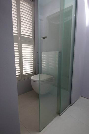 Laminated switchable smart glass in bathroom privacy door switched to clear
